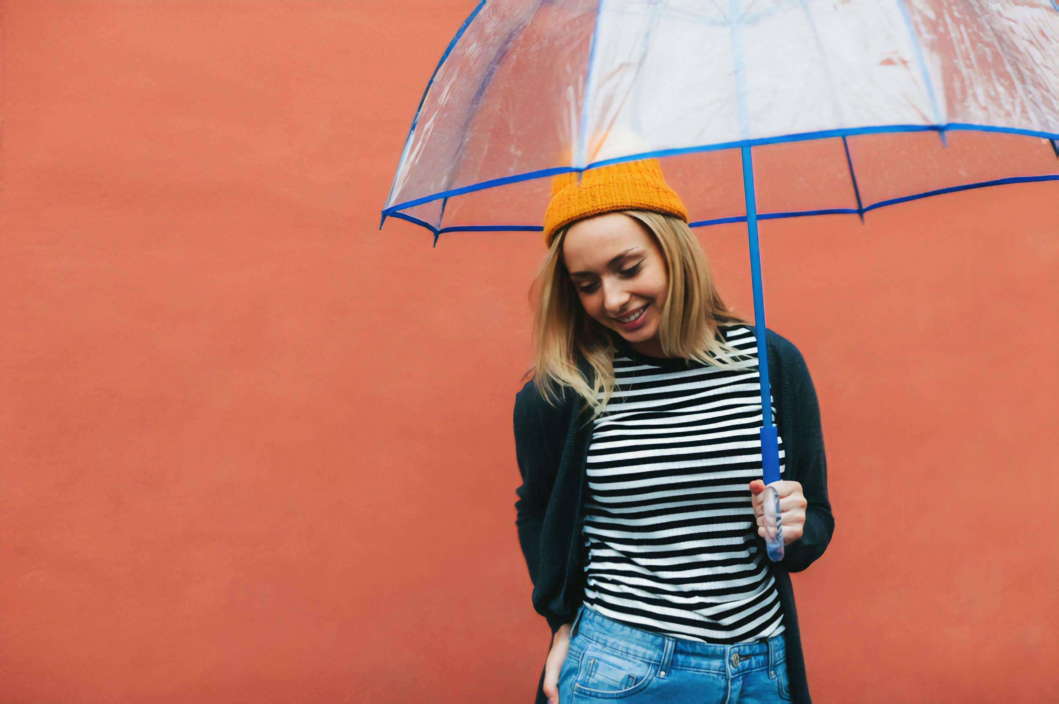 Une femme souriante tenant un parapluie